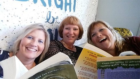 Three Staff Members Reading in the Selfie Scavenger Hunt